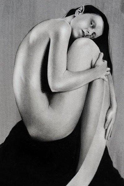 A slender mermaid sits nude, hugging her lower body.