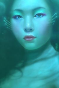 A mermaid with delicate features gazes serenely at the viewer.