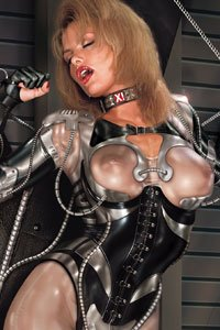 A bound blonde iwith exposed breasts beneath her transparent cyber armor.